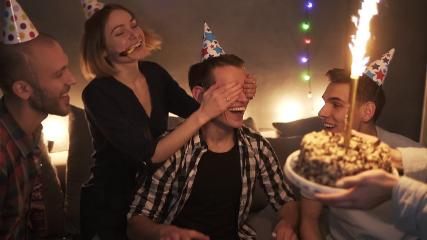 Friends in colorful caps celebrating birthday party, surprising friend with cake with burning sparkling stick. Super excited man laughing. Glitter confetti falling from the ceiling. Closest friends