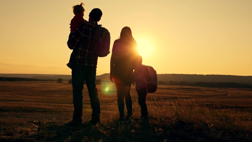 Silhouette of a family of tourists at sunset. Happy tourists mom dad boy and girl travel with backpacks on their backs. #1040473238