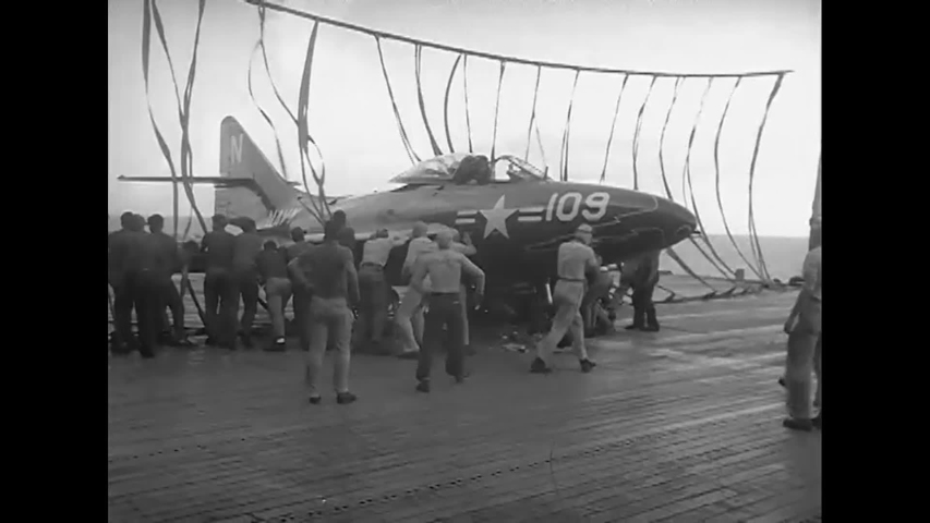 CIRCA 1954 - An F9F-6 plane is disentangled from a barrier and launched from the USS Hornet.