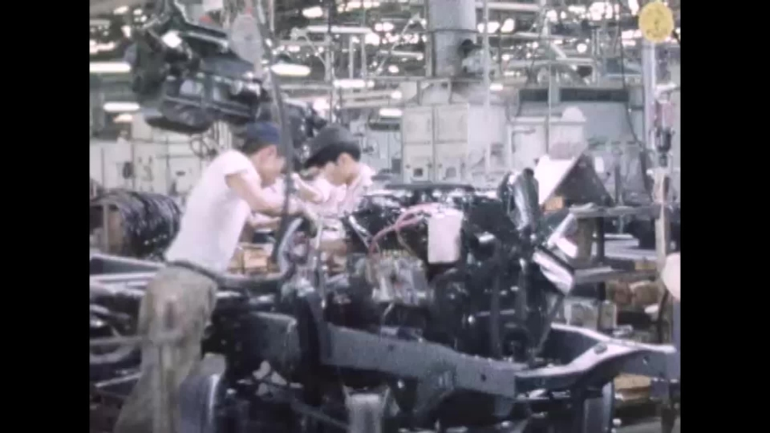 CIRCA 1960s - Workers working quickly on a truck assembly in Japan, 1960s