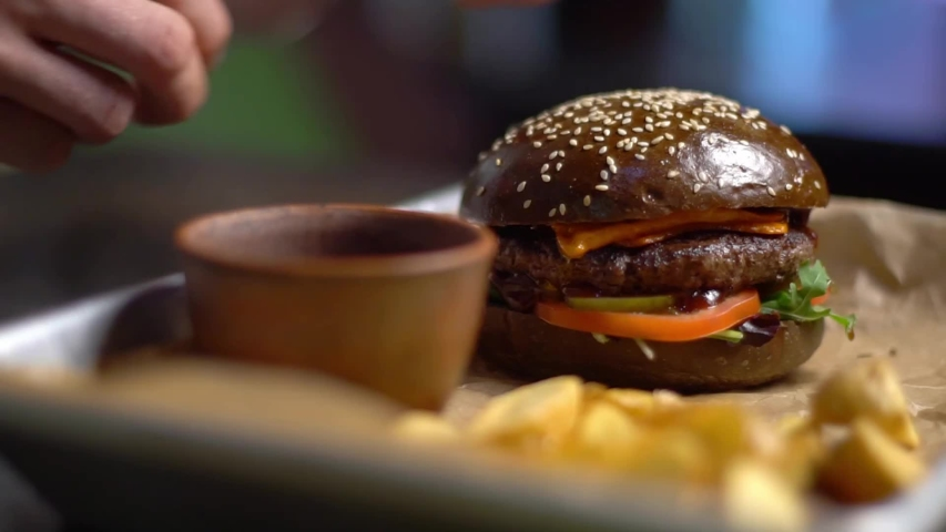 The kitchen of a fast food restaurant. Cooking in fast food restaurants. A man picks up a burger from a tray. | Shutterstock HD Video #1040495639