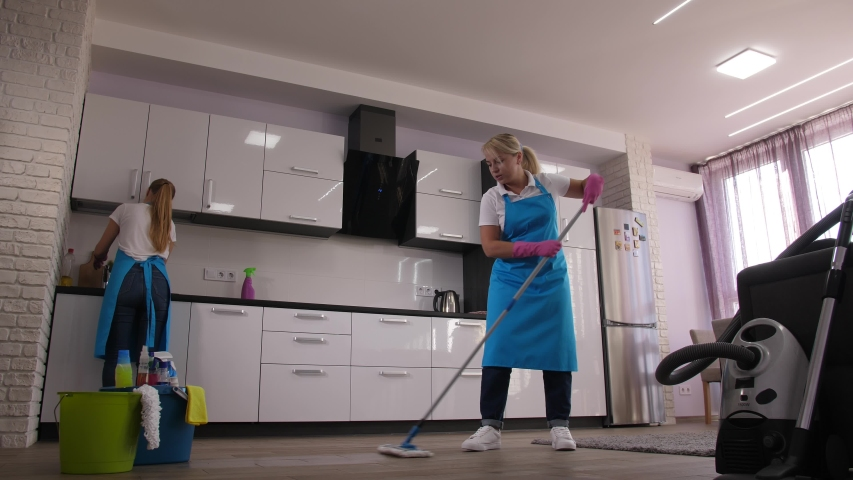 Time lapse of home cleaning services, cleaning ladies mopping floor, vacuuming carpet, washing sink, wiping kitchen surfaces in apartment. Skillful employees of cleaning company during work Royalty-Free Stock Footage #1040500580