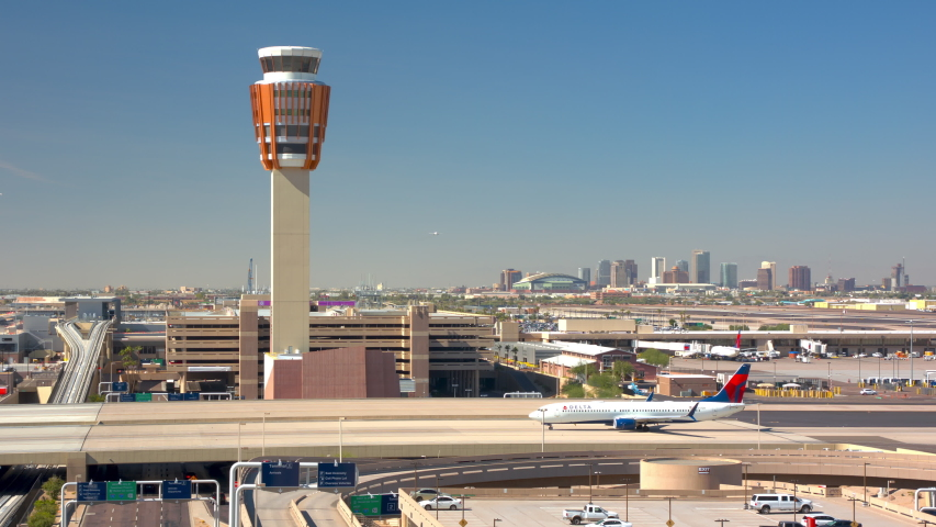 PHOENIX, AZ - 2019: Wide Airport Landscape with Delta Air Lines Boeing 737-900 Jet Airliner Taxiing Past Air Traffic Control ATC Tower in front of a Downtown Cityscape Background on a Sunny Day