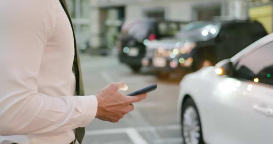 Asian businessman unlock door of car by using smart phone