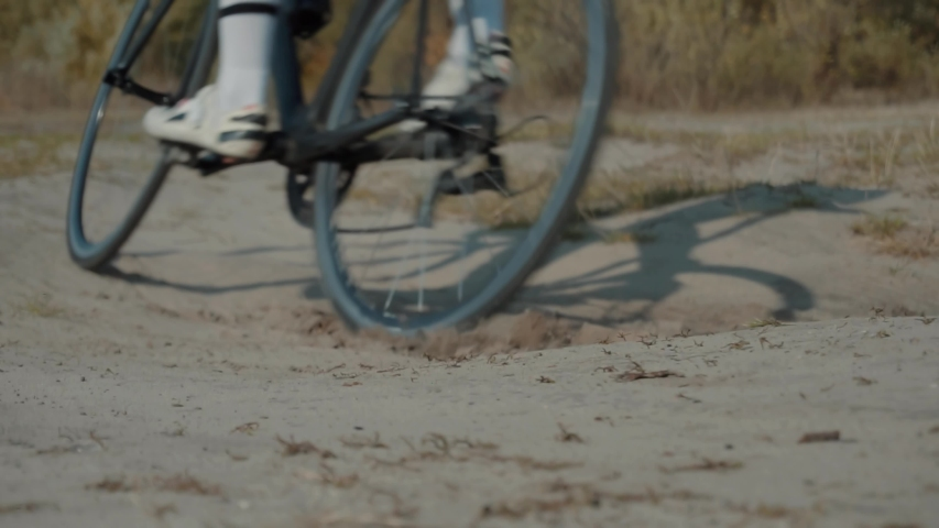 Cyclist Riding On Gravel Bike In Slow Motion.Leader On  Race Hurries To Finish Line.Cycling Race On Gravel Road.Bicycle Racing On Trail. Strong Professional Cyclist Athlete On Crosscoutry Competition