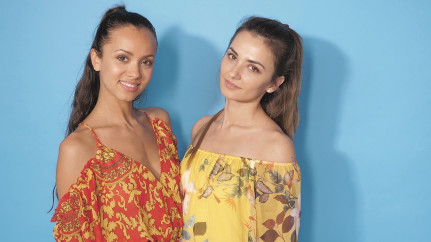 Two young beautiful smiling hipster girls in trendy summer clothes.Sexy carefree women posing in studio near blue wall.Positive models dancing