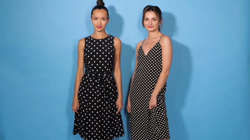 Two young beautiful smiling girls in trendy summer polka dot dresses.Sexy carefree women posing in studio near blue wall.Positive models dancing and going crazy