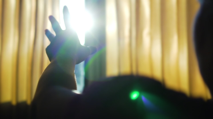 Slow motion, asian woman's hand reaching the sunlight, she looks at the sun through her hand in the bedroom. The sun shine through the hand.