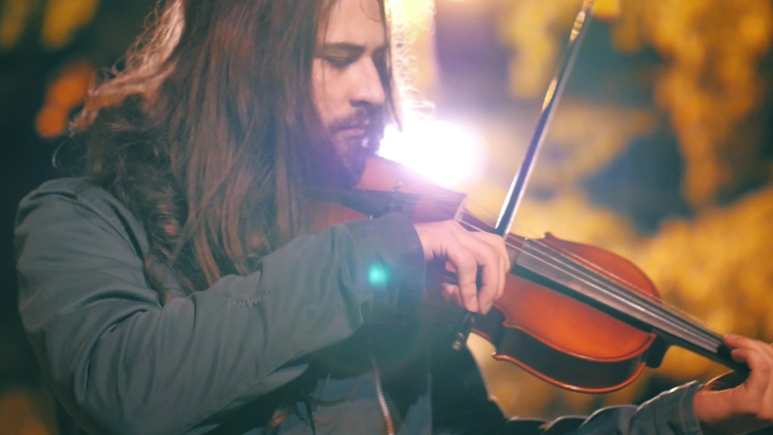 Handsome street musician rock violinist playing classical wooden violin, illuminated autumn city street in background. Closeup, shallow DOF, 4K UHD.	  | Shutterstock HD Video #1040533838