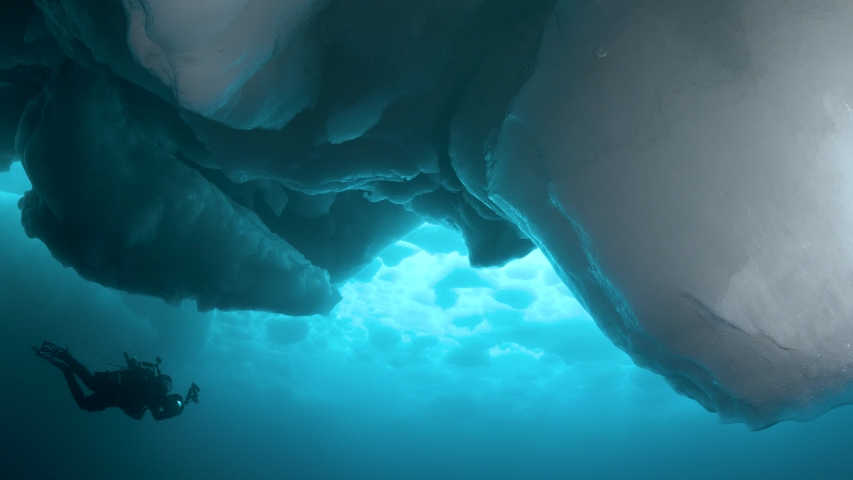 a scuba diver photographs moodful scenery under impressive icebergs