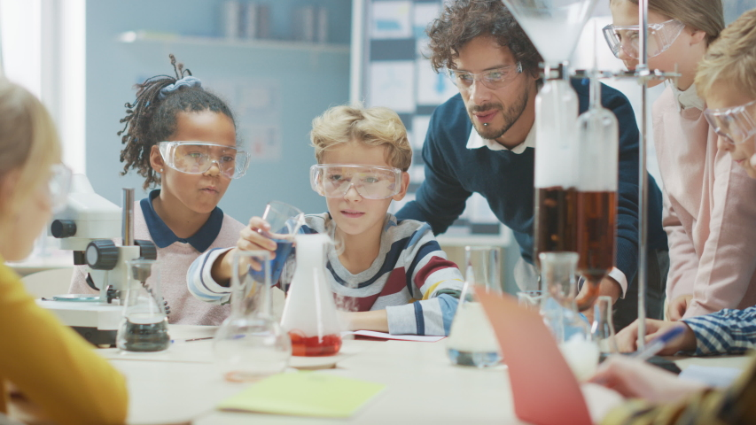 Elementary School Science Classroom: Enthusiastic Teacher Explains Chemistry to Diverse Group of Children, Little Boy Mixes Chemicals in Beakers. Children Learn with Interest