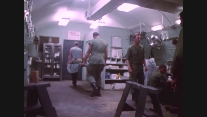 CIRCA 1968 - US Marine medical corpsmen cut away pant legs and shoes from patients in a field hospital. Other patients are loaded onto helicopters. | Shutterstock HD Video #1040579213