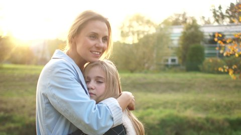 Happy mother and her teenage daughter cuddle on a walk in the autumn park at sunset. Mother and daughter, mothers day
