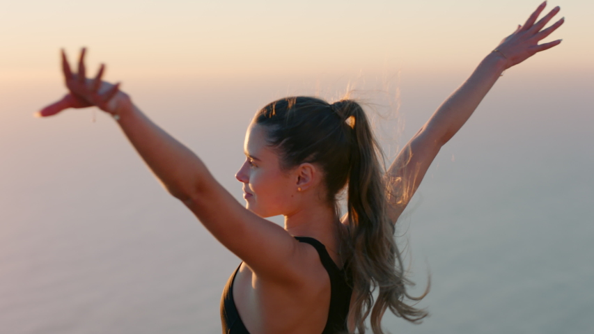 independent woman with arms raised on mountain top celebrating achievement girl on edge of cliff looking at beautiful view at sunset enjoying travel adventure #1040611970