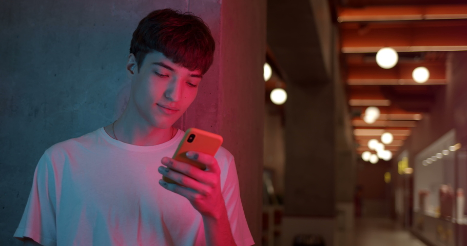 Young Stylish Millenial Boy in White T-Shirt Using his Smartphone for Chatting, Typing Messages while Standing at Futuristic Neon Club Lights Background. Close Up Shot.