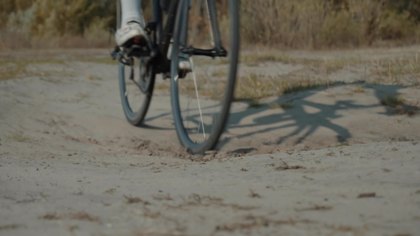 Cycling Race On Gravel Road.Cyclist Riding On Gravel Bike In Slow Motion.Bicycle Racing On Trail. Leader On  Race Hurries To Finish Line.Strong Professional Cyclist Athlete On Crosscoutry Competition