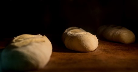 Warm fresh baguette in a bakery. Making bread and eco production. Manufacturing process working hard. Bakery shop and selling rooty. Baking Italian bio bread in oven. Time lapse footage of cooking.