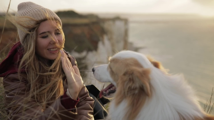 Portrait of young woman girl give five to dog and hold her paw. best friend on a cliff in Normandy on the background of the sea and sunset. slow motion. lifestyle   Shutterstock HD Video #1040648228