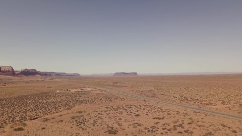 Aerial wide shot of road with view of Monument Valley with blue sky on sunny day beautiful holiday destination. Sagebrush in desert with giant butte