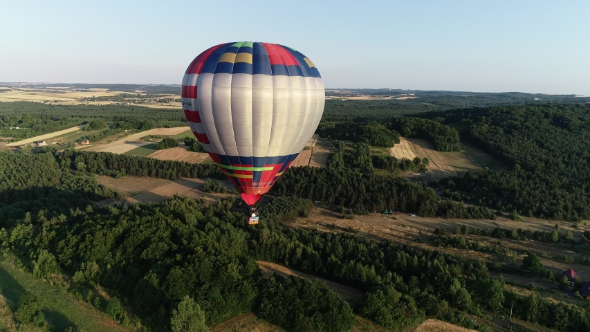 Aerial view of colorful hot air ballon flying in the sky in beautiful European scenery in the valley. Concept: adventure, proposal and engagement ideas, romantic time for couple