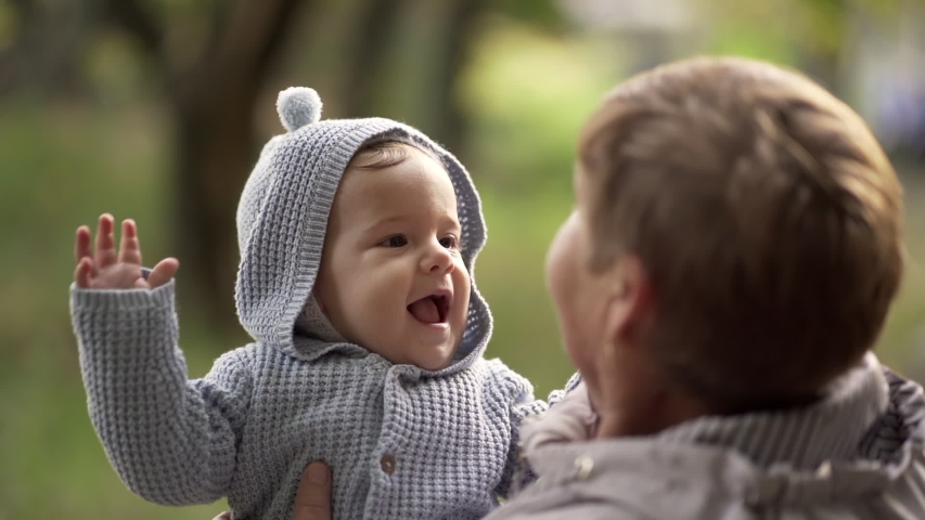Grandmother with baby boy in autumn park having fun, smiling, playing. Grandson is happy to communicate with elderly great-grandmother | Shutterstock HD Video #1040682077