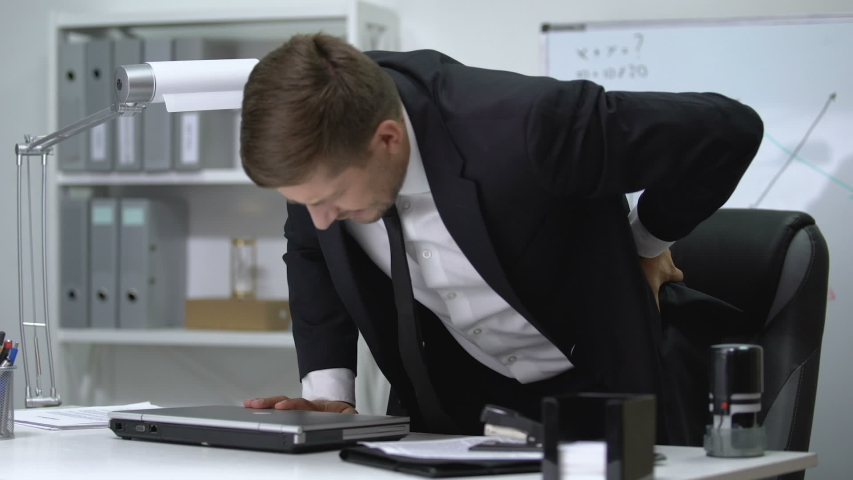 Male boss finishing work on laptop and standing up then feeling strong pain in back.