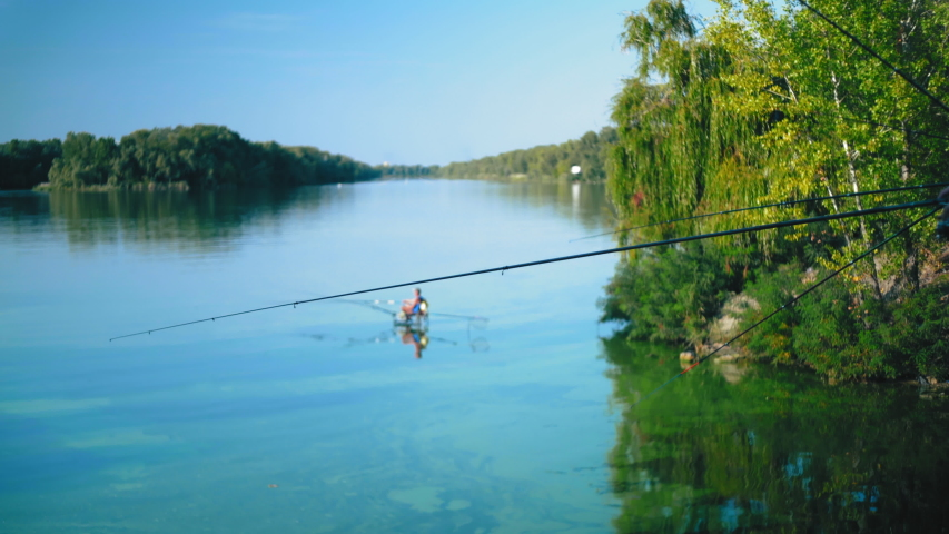 Many fishing rods fishing from the river bridge on the background of a lonely fisherman | Shutterstock HD Video #1040689103