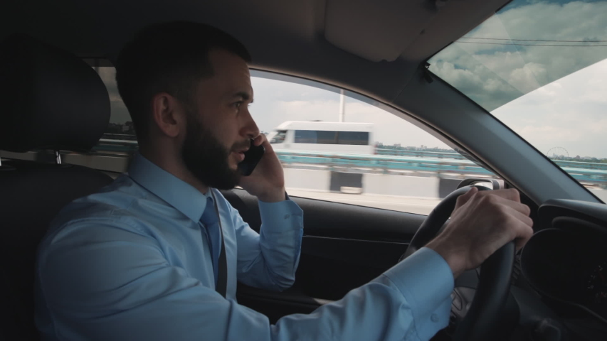 Handsome businessman talking on mobile phone and watching at road while driving car. American young man having business talk, holding steering wheel in hand sitting in black interior of automobile | Shutterstock HD Video #1040697689