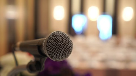 Microphone on seminar in meeting conference hall for speaker at podium presentation, abstract blurred of speech in communication, speaking room with audience chairs, Talk business of event background