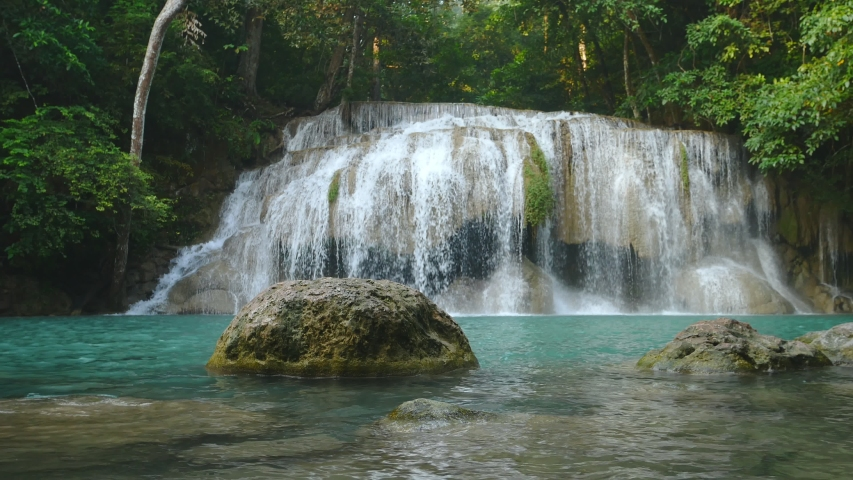 Natural scenery of beautiful Erawan waterfalls in a tropical rainforest environment and clear emerald water. Amazing nature for adventurers Erawan National Park, Thailand | Shutterstock HD Video #1040707487