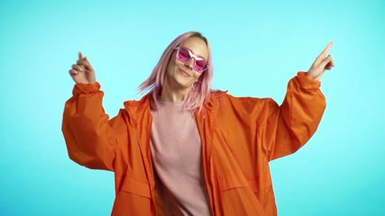 Funny unusual woman with pink hair having fun, smiling, dancing in studio against blue background. Music, dance concept, slow motion