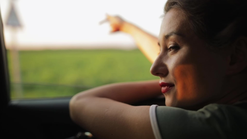 Cinematic inspirational video of young woman travelling by car or camper van, opens window to breathe fresh air of countryside, moves hand in wind. Sings melody of song, summertime vacation vibes Royalty-Free Stock Footage #1040716850