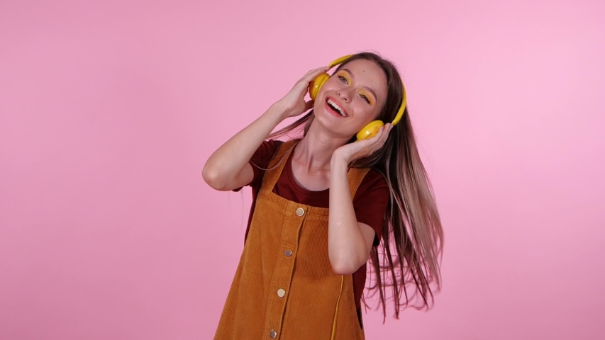 Happy teenage girl with headphones listening to music on pink background. Slow motion effect | Shutterstock HD Video #1040717486