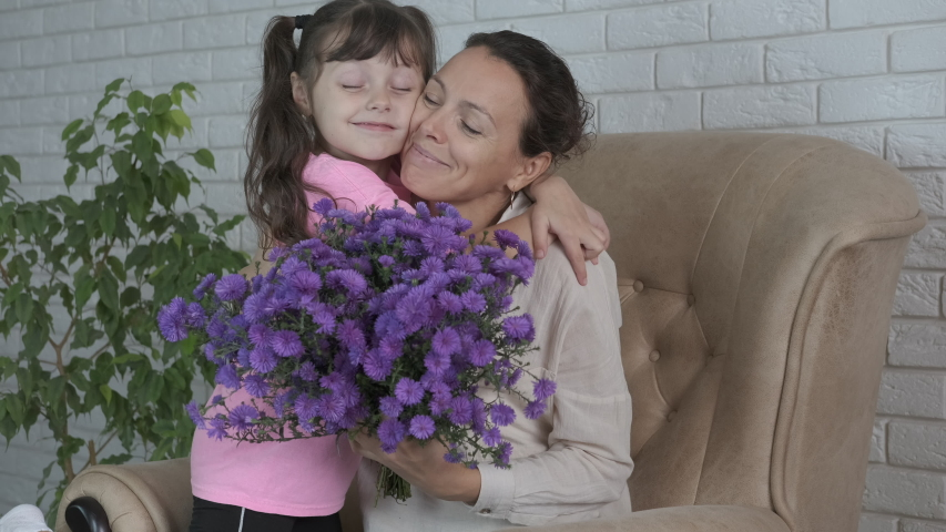 Kid give a bouquet. Cute kid give a surprise to her mother. A bouquet of blue flowers for a mum.