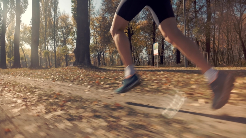 Triathlete Running,Sprinting And Endurance Workout Training.Marathon Runner Jog On Park.Running Man In Forest At Sunset.Runner Man Fit Athlete Legs Jogging On Trail Ready To Triathlon.Sport Concept. | Shutterstock HD Video #1040730422