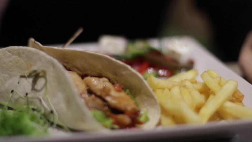A pretty girl eats food in a restaurant | Shutterstock HD Video #1040733821