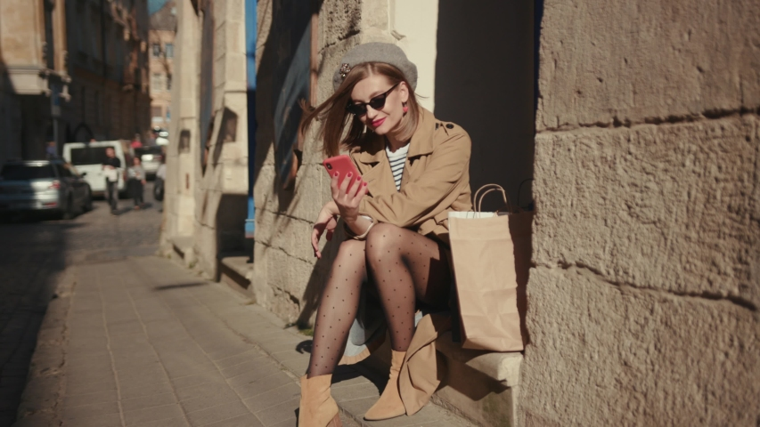 Sexy young woman wearing stylish coat in a bright sunlight uses phone sitting in the city center looks around smile happy summer internet business outside technology mobile slow motion #1040737922