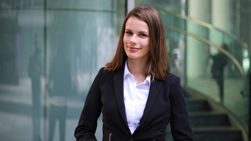 Young businesswoman welcoming you in a modern city setting | Shutterstock HD Video #1040740994