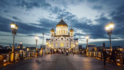 Amazing hyperlapse of the Cathedral of Christ the Saviour in Moscow on the evening. Camera moving along the beautiful bridge towards the church all in glittering lights, night city on the background.