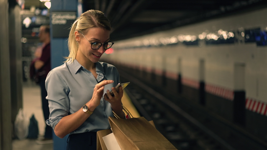 Smiling female passenger with shopping bags standing in subway and waiting for metro transport while checking timetable at online website for public using, happy hipster girl in eyewear with cellphone