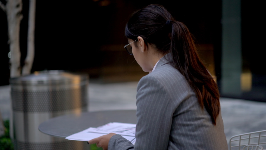 Latin female trader using mobile phone for making international cell call with operator during financial accounting in downtown, Hispanic woman in glasses checking trade money report and phoning  | Shutterstock HD Video #1040764724