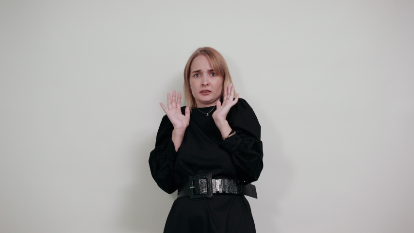 Portrait of scared shocked young woman in casual clothes screaming, rising hands showing palms isolated on white wall background in studio. People sincere emotions lifestyle concept.