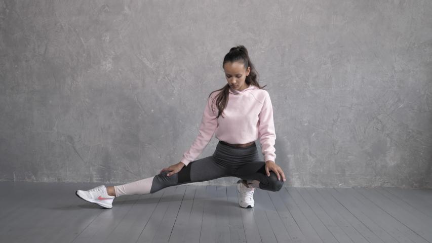 BELARUS, MINSK - OCTOBER 1, 2019: Pretty woman wearing sportswear.Beautiful girl stretching after training in studio.Healthy and sport lifestyle | Shutterstock HD Video #1040778164