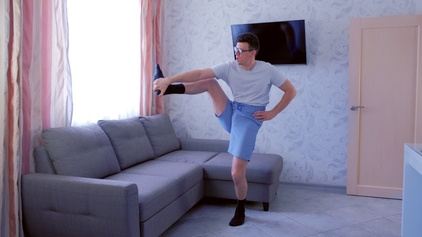 Funny nerd man in glasses and shorts is doing forward slopes and stretching exercises for legs at home. Sport humor concept. | Shutterstock HD Video #1040786990