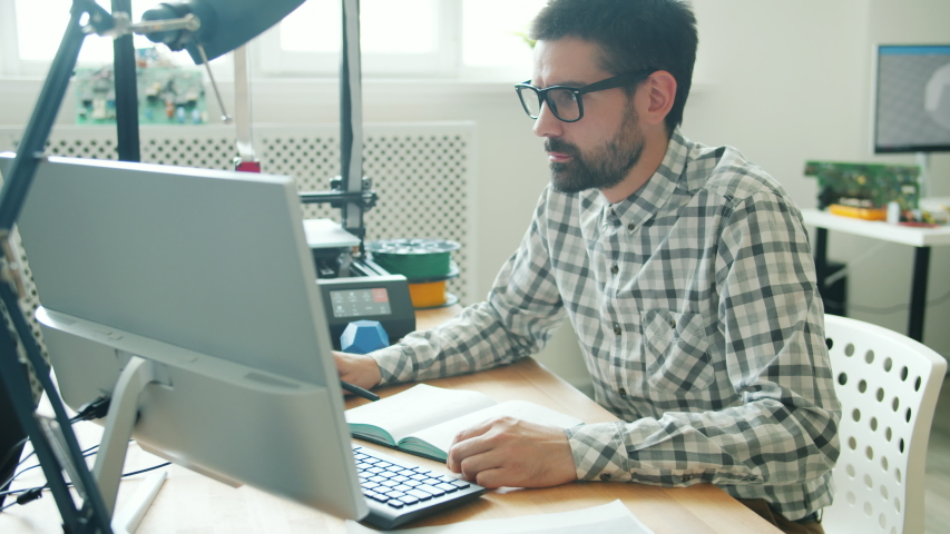 Slow motion of serious young man in glasses using computer and making 3d printer element in modern office. Technology and contemporary business concept.
