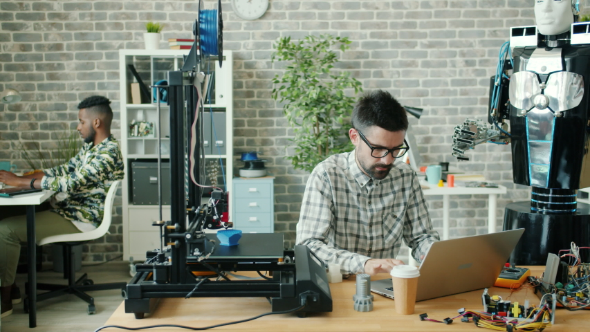 Young developer serious guy is using laptop typing in office, 3d printer and robot are visible in workplace. People, modern technology and contemporary business concept.