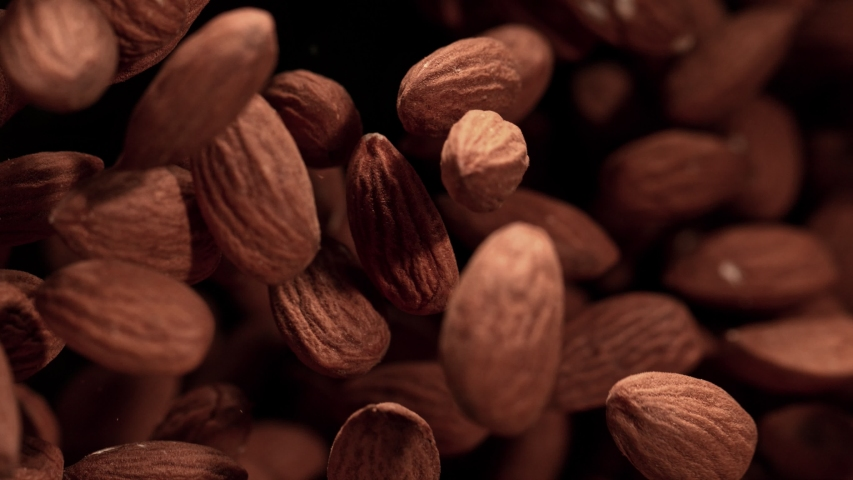 Super Slow Motion Shot of Almonds Flies After Being Exploded against Black Background, 1000fps.