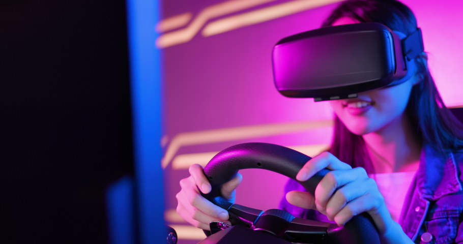 Asian girl play car racing game with wearing vr glasses