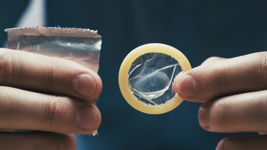 Male hands take out a condom from the packaging. Contraception and protected sex concept