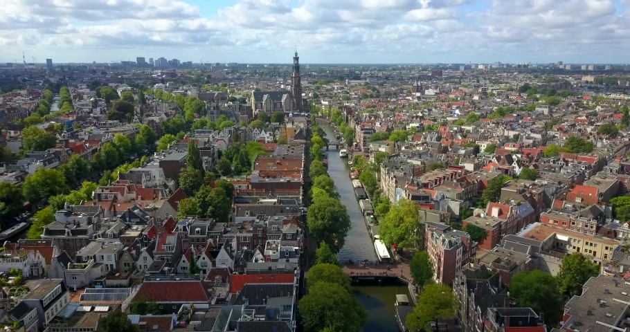 Amsterdam,  Netherlands. Aerial top view of the city centre, surrounded by picturesque houses with red roofs, green trees and canal  | Shutterstock HD Video #1040846570